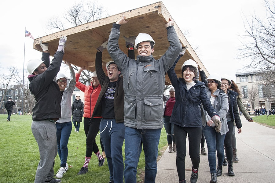 Image of students during carrying construction materials